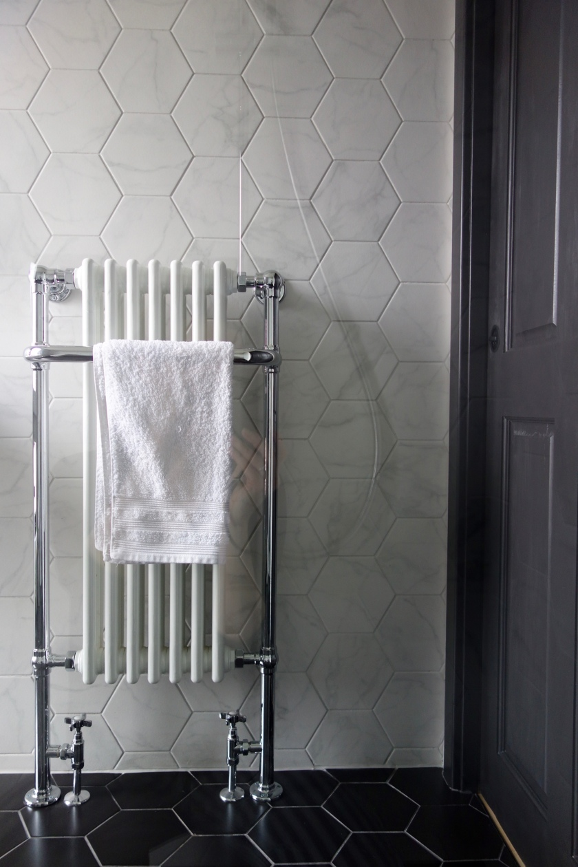 Column Towel Heater with marble hex tiles and black pocket door